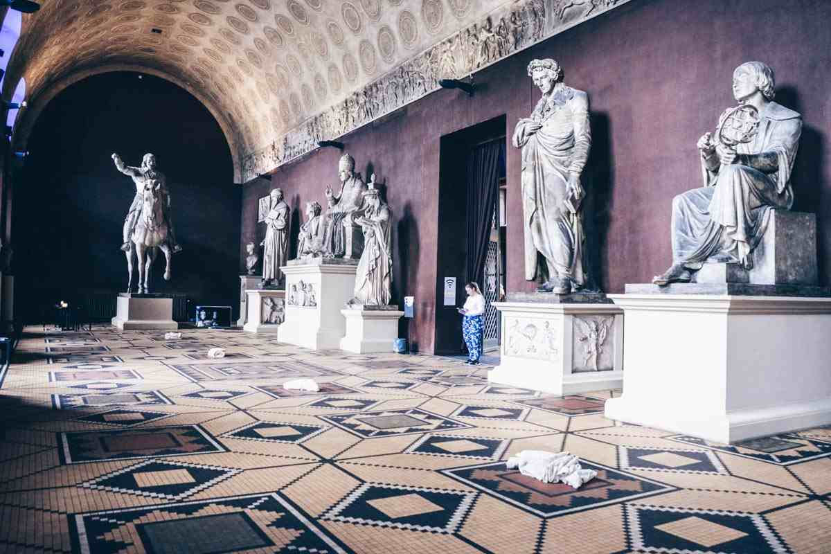 Massive Greek-style sculptures on display inside the Great Hall of Thorvaldsen's Museum