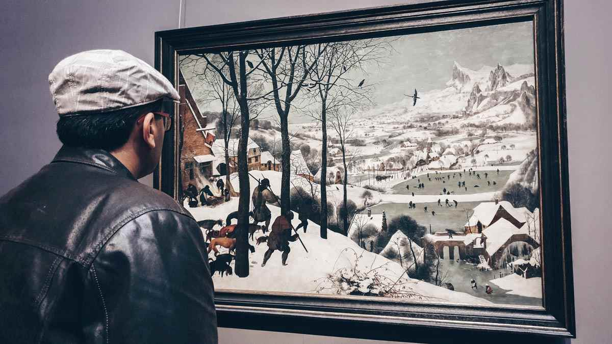 """Man admiring Bruegel's captivating """"Hunters in the Snow"""" painting at the Art History Museum Vienna"""
