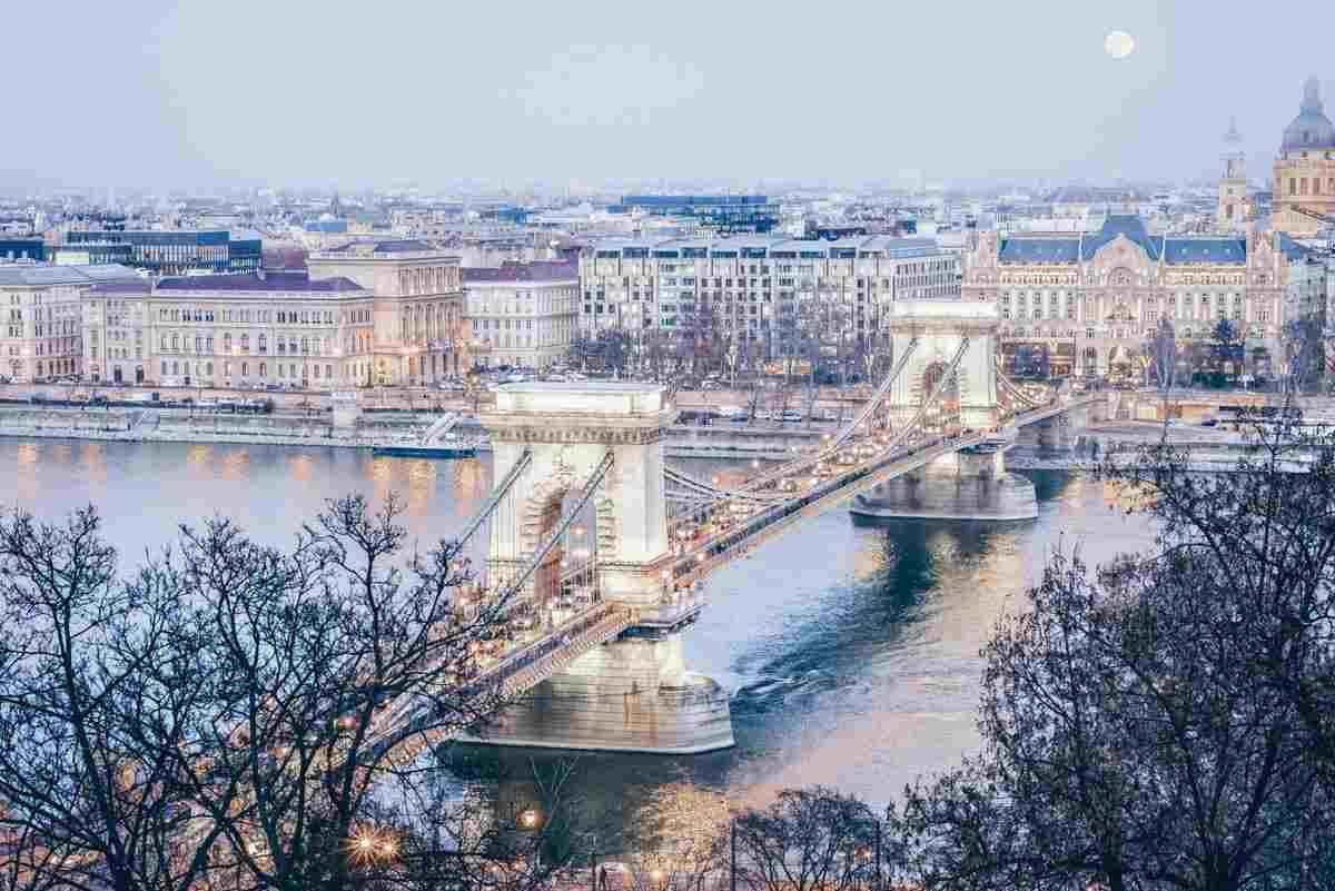 Things to see in Budapest: View of the Danube River and the glittering iconic Szechenyi Chain Bridge in winter