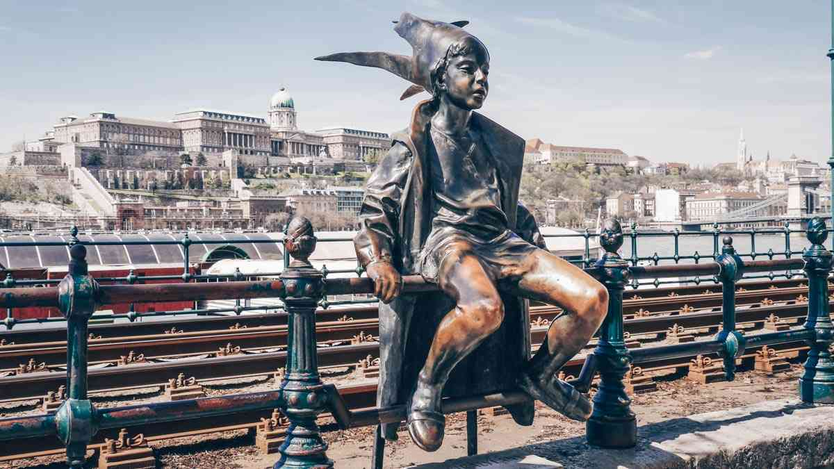 Budapest attractions: View of the impish Little Princess Statue with the Danube and Buda Castle in background