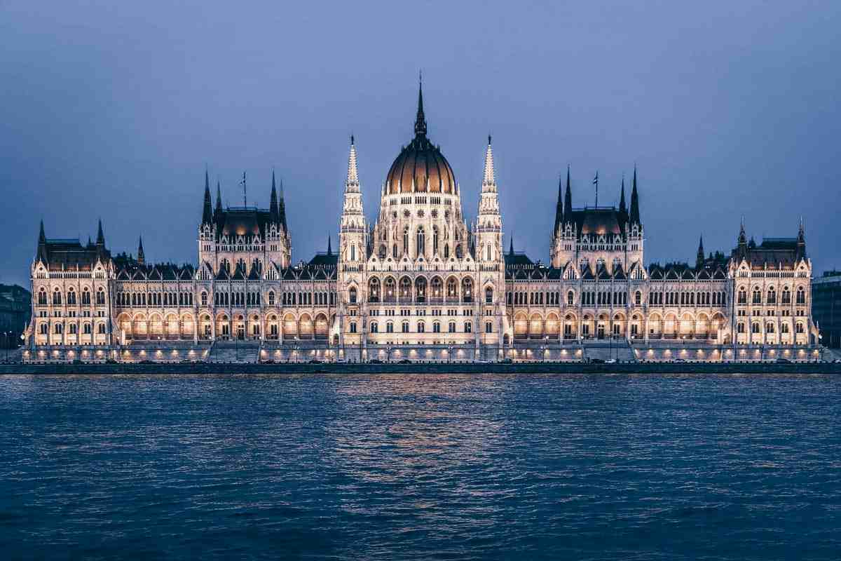 The lit-up exterior of the Hungarian Parliament Building in the evening across the Danube