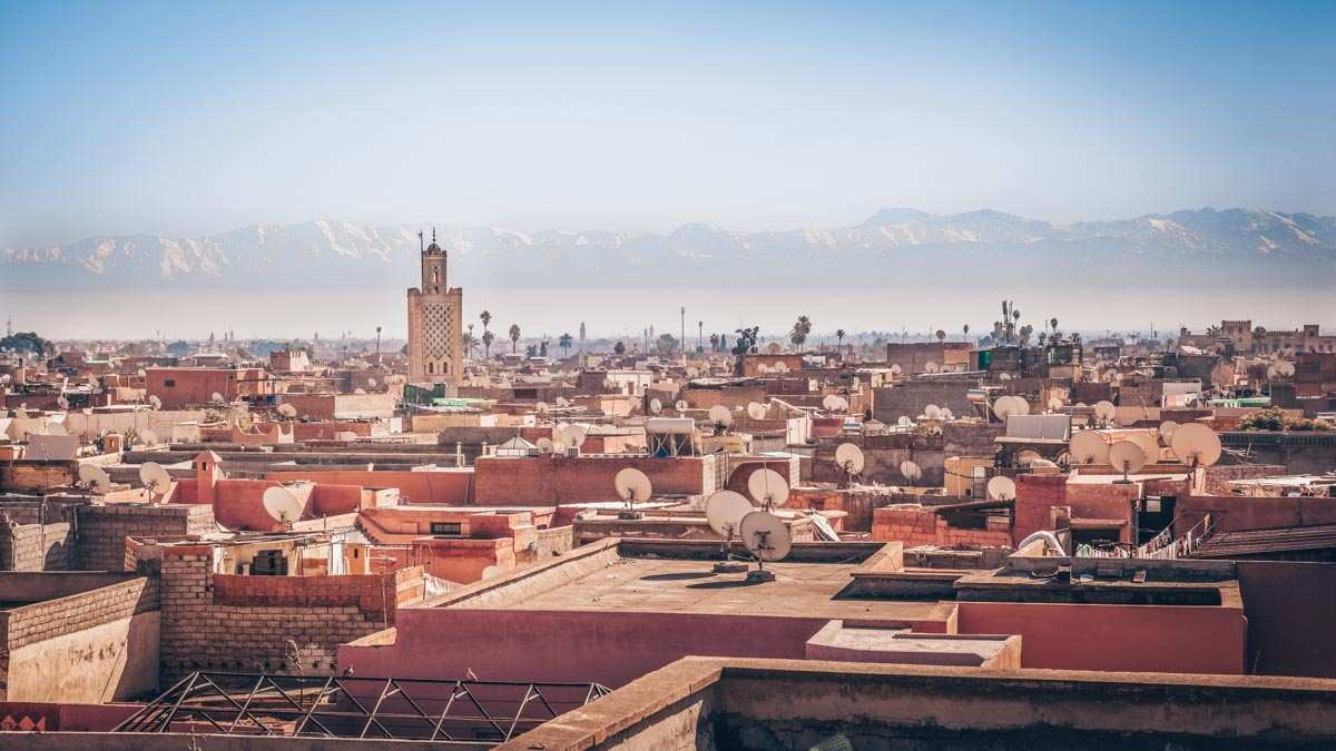 TMarrakech: Panoramic view of the red-roofed buildings with the Atlas Mountains in the background.