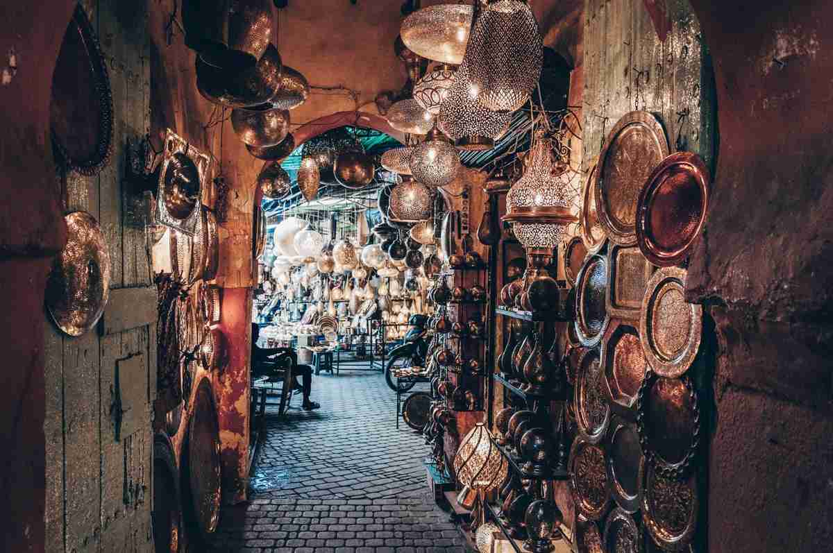 Marrakech Souks: Illuminated lanterns and copper plates on display in a narrow alley