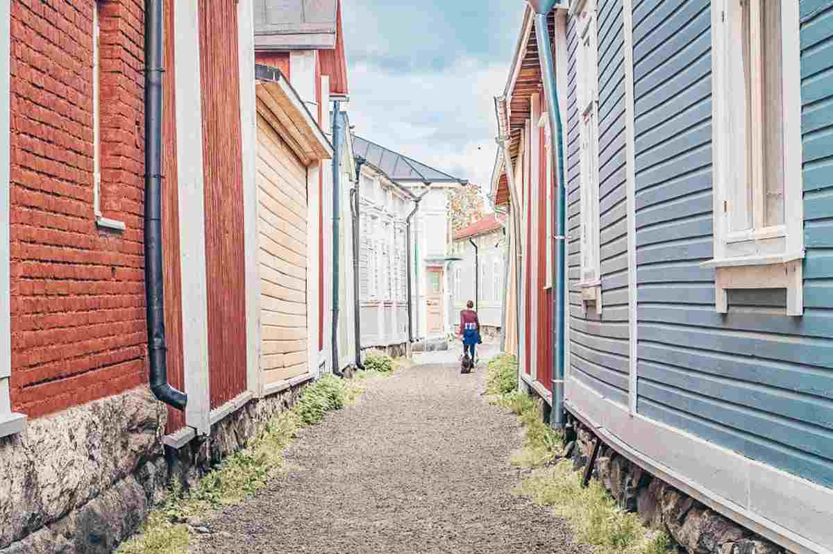 Rauma: Woman walking through a narrow alley between colorful wooden houses