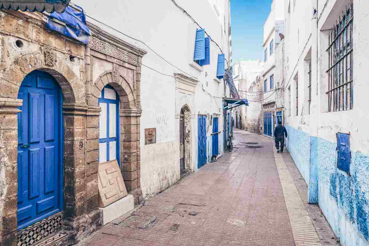 Essaouira: Man walking on a narrow alley surrounded by whitewashed buildings. PC: Checco2/Shutterstock.com