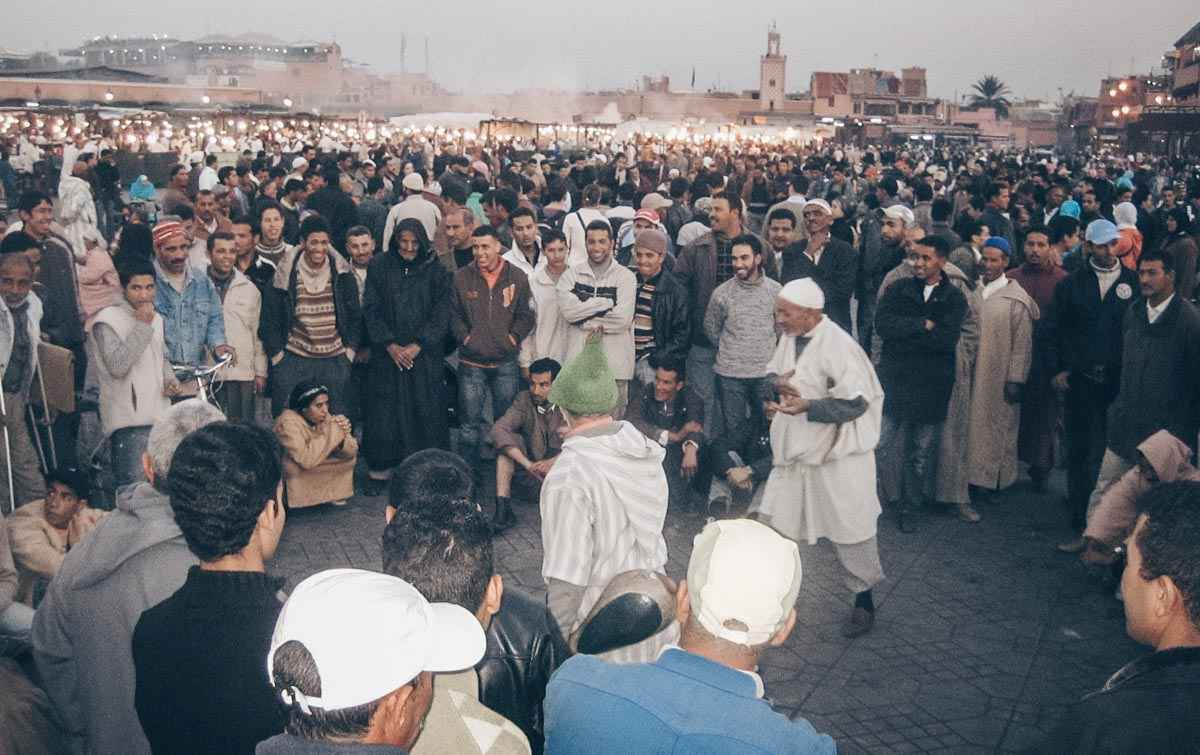 Marrakech: A crowd of people listening intently to a storyteller at Jemaa el Fna in the evening