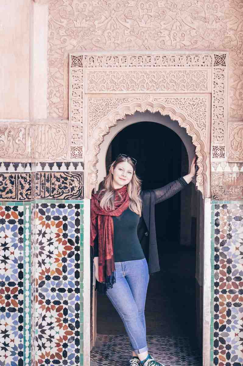 Marrakech: Beautiful blonde woman posing for a photo in the carved stucco archway of Ben Youssef Medersa