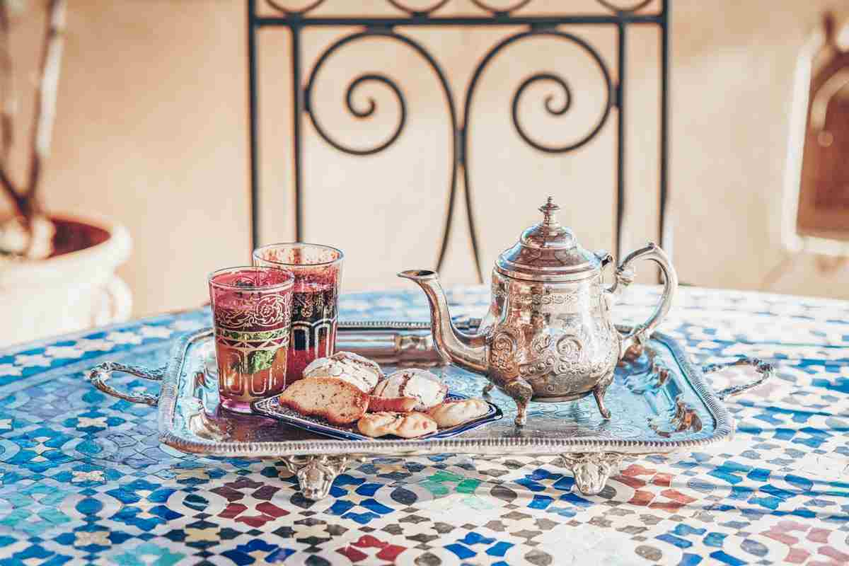 Traditional Moroccan mint tea in ornamental glasses beside a silver teapot