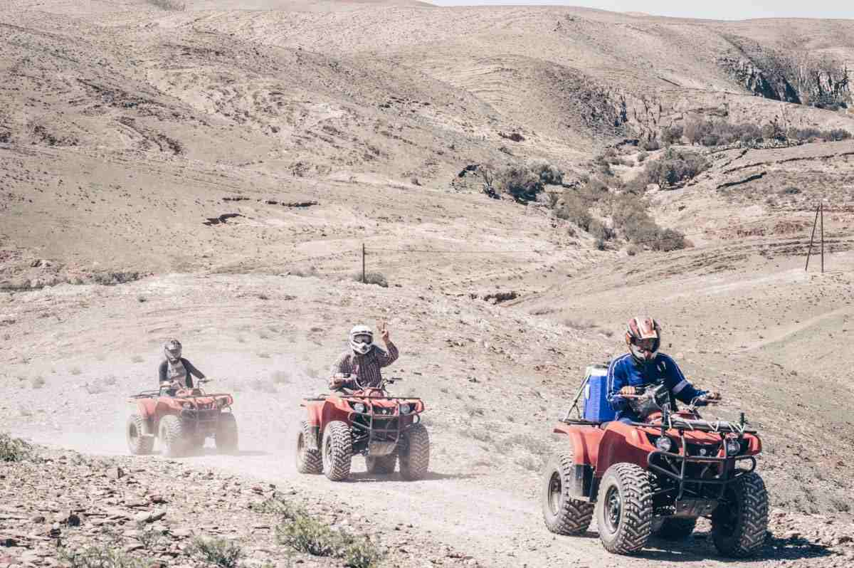 Three individuals on quad bikes in the Agafay Desert in the afternoon