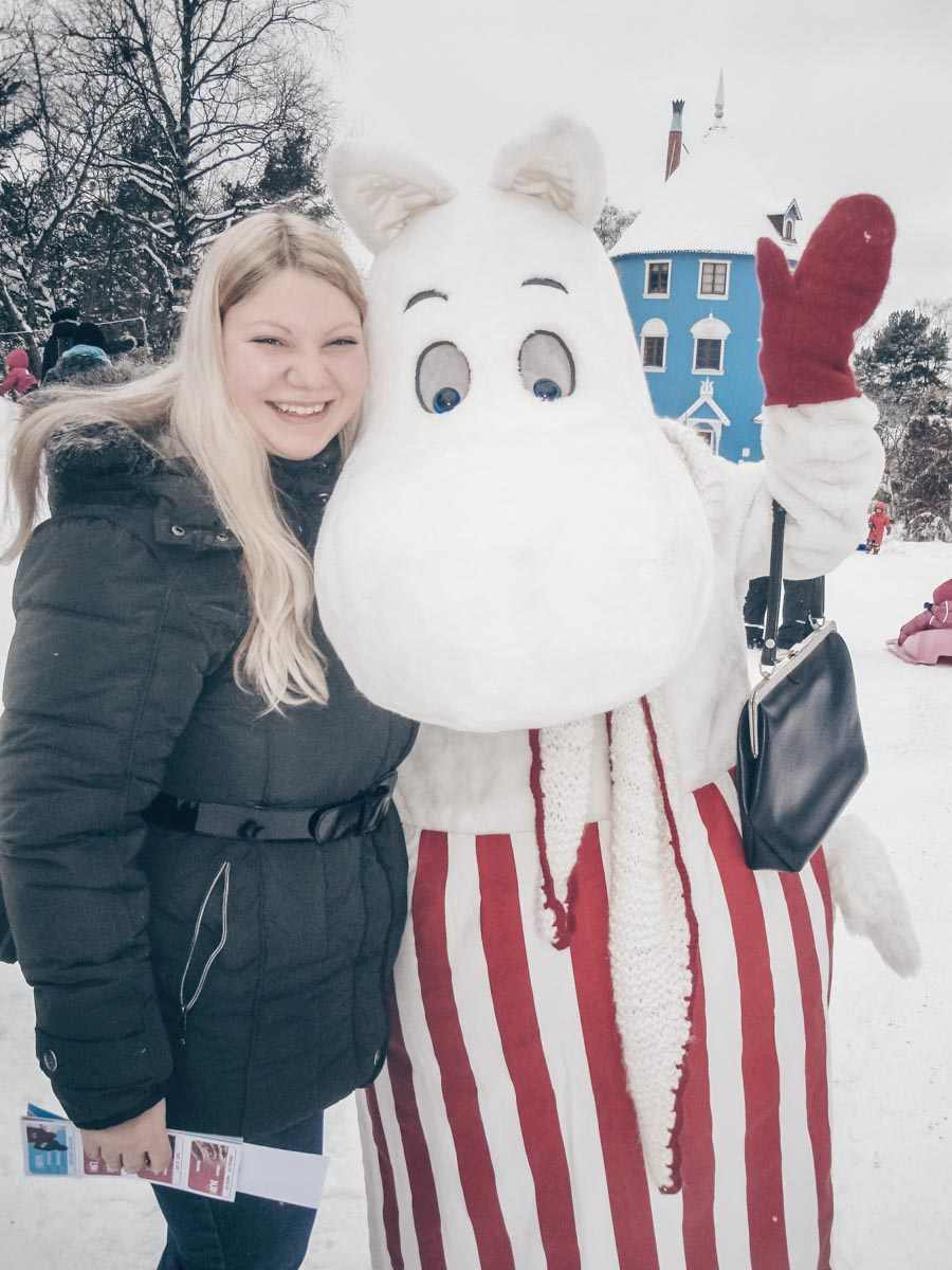 Naantali Moominworld: Beautiful blonde girl posing for a photo with a Moomin mascot